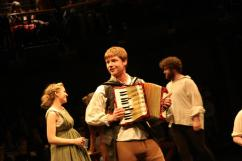 An accordion is played in the middle of a group scene.