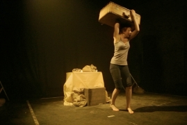 A woman on a barren stage desperately holds a suitcase above her head.