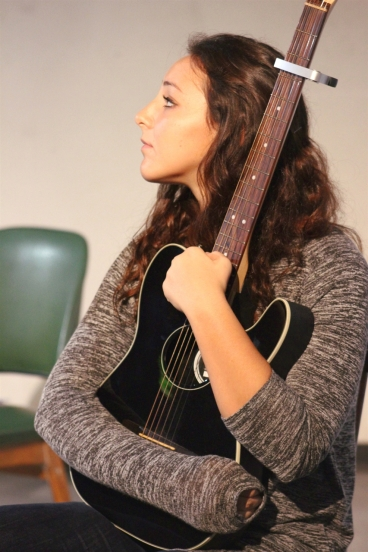 A woman holds a guitar close to her chest.