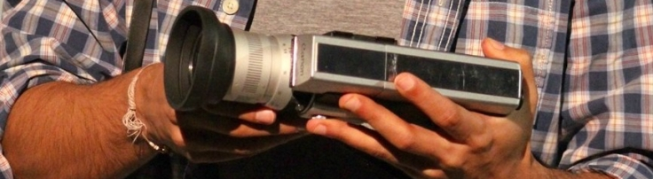 A pair of hands gently hold a Super 8 camera.