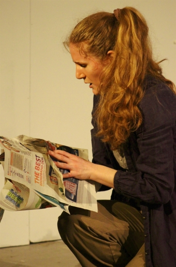 A woman searches through newspapers for information.