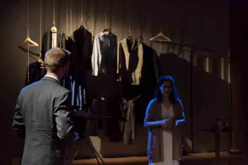 On a darkened stage, a suited man approaches a nervous-looking woman.