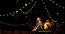 Two women, one playing a guitar, sit on a raised platform surrounded by festoon lights.
