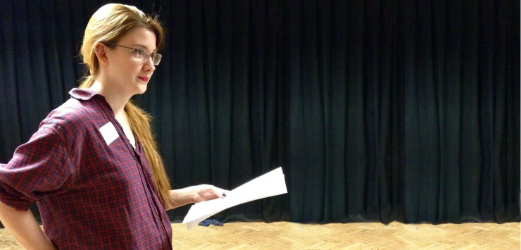 A woman stands holding a script in a rehearsal room whilst looking out of shot