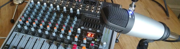 An image of a sound desk and condenser mic on a tabletop